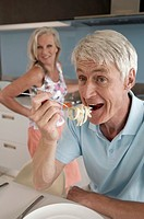 Close-up of a senior man eating noodles with a senior woman smiling in the background