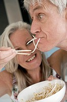 Close-up of a senior woman feeding bean sprouts to a senior man