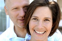 Portrait of a mature woman smiling with a mature man behind her