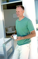 Mature man leaning against a column holding a cup of coffee