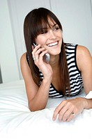Close-up of a mid adult woman lying on the bed and talking on a mobile phone