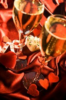 High angle view of champagne flutes with a heart shaped candle