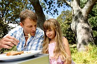 Close-up of a girl sitting with her father at a picnic table