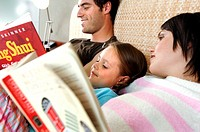 Close-up of a mid adult couple with their daughter lying on the bed and reading books