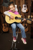 Seated girl playing acoustic guitar