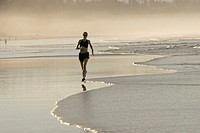 A woman jogging along a beach