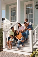Two families sitting on front porch together
