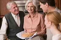 Woman presenting pie to family