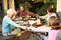 Family praying at outdoor table before meal