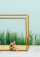 Woman sitting in square structure, body of water in background