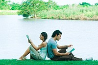 Couple sitting near edge of water, back to back, reading