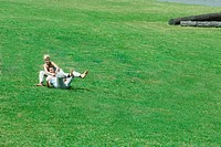 Couple sitting on grass together, man leaning back on woman
