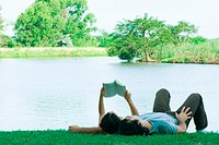 Couple lying on grass near lake, reading