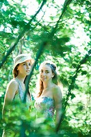 Two young women standing among trees