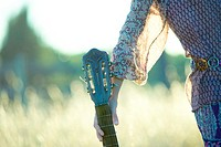 Young hippie woman holding guitar, cropped view of mid section