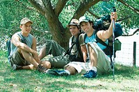 Three hikers sitting under tree