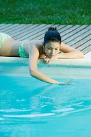 Young woman lying next to pool, touching water (thumbnail)
