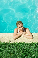 Young woman resting arms on edge of pool