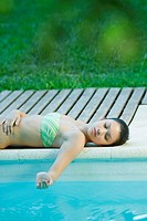 Young woman lying by edge of pool, holding water in cupped hand (thumbnail)