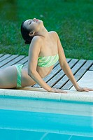Young woman next to pool, on stomach, head back