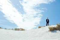 Businessman standing on dune with hands in pockets, low angle view