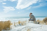 Woman sitting on dune, using cell phone, rear view