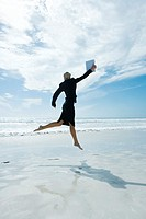 Businesswoman jumping in air on beach, holding up file