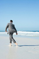Barefoot businessman walking across beach