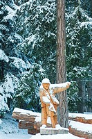 Wooden lumberjack by timber in snow