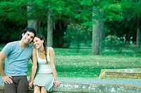 Couple sitting outdoors, heads together, smiling