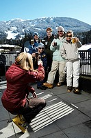 Woman photographing five adults in ski-wear drinking beer on balcony