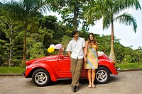 Couple leaning against convertible car on road with palm trees