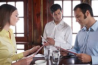 Waiter taking couples orders in restaurant