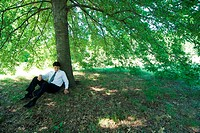 Businessman sitting under tree