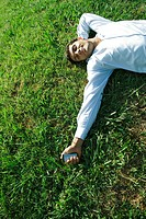 Businessman lying on grass, holding cell phone, eyes closed, smiling