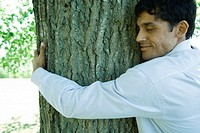 Businessman hugging tree