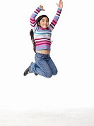 Girl 8-9 leaping with arms raised, on white background, portrait