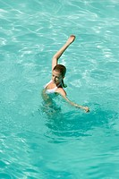 Young woman standing in pool, stretching arms, full length, high angle view