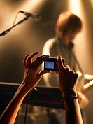 Person photographing musician at concert