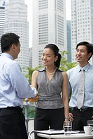 Businesspeople shaking hands at outdoors cafe