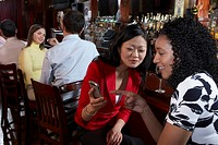 Two women observing mobile phone at bar