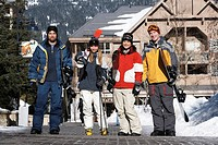 Four adults with skis and snowboards, portrait