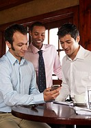 Three men observing mobile phone in restaurant