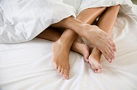 ´Couple lying in bed, close up of touching feet´