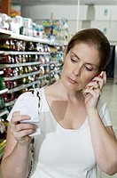 Woman using mobile telephone in supermarket, looking at shopping list