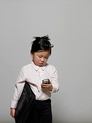 Girl 3-5 dressed as businesswoman looking at mobile phone message