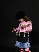Girl 5-7 holding artist palette putting brush in smock pocket