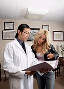 Male acupuncturist and female patient looking at medical chart
