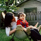 Woman sitting with daughter in lawn chair