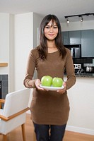 Woman holding plate of apples